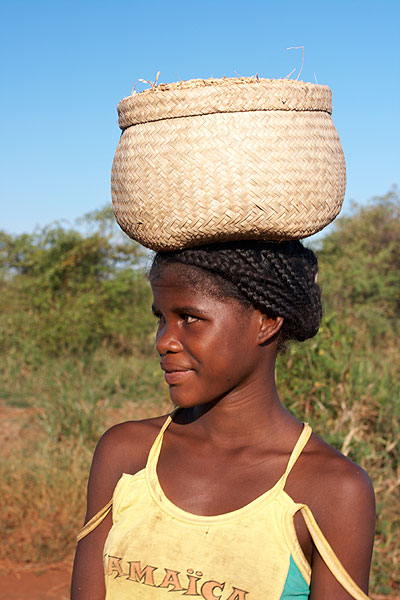 Mladá žena s košem na hlavě