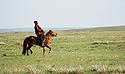 Mongolský pastevec na koni